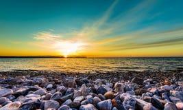 Steine auf einem Strand mit Sonnenuntergang auf dem Ozeanmeer Stockfotografie
