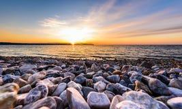 Steine auf einem Strand mit Sonnenuntergang auf dem Ozeanmeer Lizenzfreie Stockfotografie