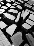 Steine auf einer Fußgängerstraße, die kontrastierendes helles Muster schafft Stockbild