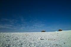 Steine auf Schneefeld im blauen Himmel Stockfoto