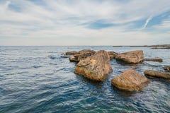 Steine auf Strand, Meer und blauem Himmel. Lizenzfreies Stockbild