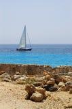 Steine auf Strand und Yacht Stockfotografie