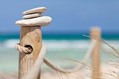 Steine balancierten auf hölzerner Geländerdocke nahe dem Strand. lizenzfreies stockfoto