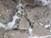 Steine des Granits auf Schneehintergrundbeschaffenheit, schneebedeckte Steine nahe Gebirgsfluß, schneebedecktes Land lizenzfreie stockfotos