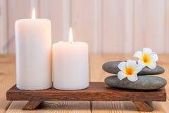Steine für Massage und Frangipaniblumen in der Zusammensetzung Stockfotografie