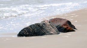 Steine gegen eine Seebrandung Stockfotos