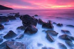 Steine im Meer am Sonnenuntergang Lizenzfreie Stockfotos