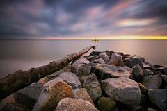 Steine im Meerwasser auf dem Hintergrund des Sonnenaufgangs Lizenzfreies Stockbild