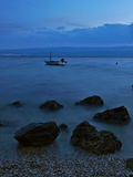 Steine und Boot in nebelhaftem Meer Stockbild