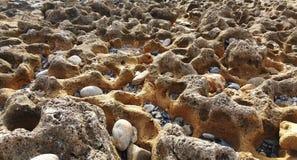 Steine und Oberteil auf dem Strand Stockfotos