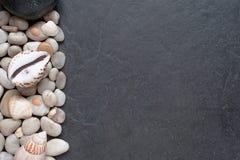 Steine und Oberteile auf einem dunklen Hintergrund Stockbilder