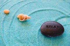 Steine und Shell auf einem blauen Sand Lizenzfreie Stockfotos