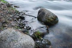 Steine unter schnellem Wasserstrom Stockfoto