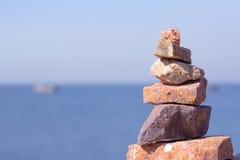 Steine werden oben auf dem Felsen an der Küste angehäuft Stockbilder