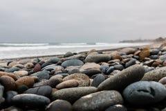 Steine zerstreut über Strand am Karlsbad-Staats-Strand Stockfotografie