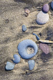 Steinformulardiagonale auf sandigem Strand Stockbild