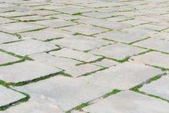 Steinfußwegenmuster mit grünem Gras im Perspektivenhintergrund Lizenzfreies Stockfoto