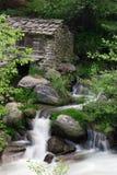 Steinhütte an einem Strom Stockfotos