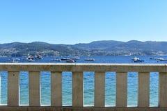 Steinhandlauf in einem Strandpromenadenhintergrund Türkiswasser, Boote in einer Bucht, blauer Himmel, sonniger Tag Galizien, Rias lizenzfreie stockfotografie