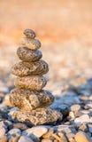Steinhaufen auf dem kieseligen Seestrand Stockbild