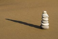 Steinhaufen von gerundeten Felsen auf nassem Strandsand Lizenzfreies Stockbild