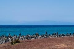 Steinhaufenfelsenkiesel auf Teneriffa setzen bei Costa Adeje, Adeje, Kanarische Inseln Teneriffas auf den Strand Stockfotografie