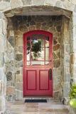 Steinhaus und rote Haustür Stockfotos