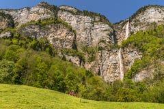 Steinige Alpenberge und ein hoher Wasserfall Lizenzfreie Stockfotos