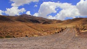 Steinige eingezäunte Straße, die trockene Hügel durchläuft stockfotos