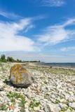 Steinige Küstenlinie gegen szenisches cloudscape Lizenzfreie Stockbilder