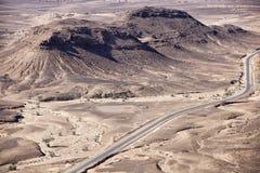 Steinige Wüste verschönert mit gepflasterter Straße, Sahara landschaftlich. Stockbild