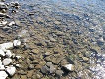Steiniger Flussgrund durch transparentes Wasser, verschiedene Größen von Steinen Stockfotos
