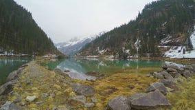Steiniger Seeufer in den Bergen, Starkstromleitungen, alternative Energiegewinnung stock video