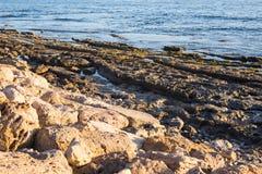 Steiniger Seeuferhintergrund Stockbilder