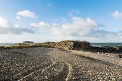 Steiniger Strand mit Reifenbahnen in den Steinen lizenzfreies stockbild