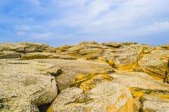 Steiniges Gelände der gelben Farbe gegen den Himmel Stockfoto