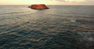 Steininsel im Meer Flug der Kamera zur Insel bei Sonnenuntergang stock footage