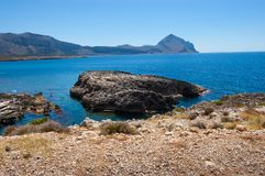 Steininsel umgeben durch klares blaues Meer lizenzfreie stockfotos