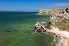 Steinklippen auf der Küste und dem blauen Himmel mit Wolken stockfoto