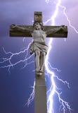 Steinkreuz mit Jesus und Himmel mit Blitz Lizenzfreies Stockfoto