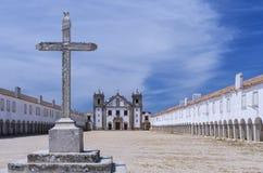 Steinkreuz vor einer barocken Kirche und einem Schongebiet Lizenzfreies Stockfoto