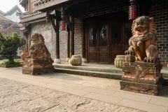 Steinlöwen am Tor des chinesischen traditionellen Gebäudes in sonnigem Achtern Lizenzfreies Stockbild