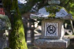 Steinlaterne mit dem Logo von zwei Vögeln in der Liebe am Tempel Tamukeyama Hachimangu in Nara, Japan lizenzfreie stockfotografie