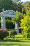 Steinlaube mit großen Säulen und dekorativer Stuck vor dem hintergrund der grünen Parkzone lizenzfreies stockbild
