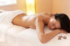 Steinmassage auf Weiß Der Brunette, der ein Salz erhält, scheuern Schönheits-Behandlung in lizenzfreies stockbild