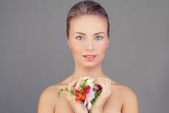 Steinmassage auf Weiß Gesunde Frau mit klarer Haut und Blumen Lizenzfreie Stockfotografie