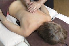 Steinmassage auf Weiß Junge Frau, die entspannende Rückenmassage in der Cosmetologybadekurortmitte genießt Körperpflege, Hautpfle stockfotos