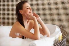Steinmassage auf Weiß Schönes Mädchen, das ihr Gesicht berührt Vollkommene Haut Skinc lizenzfreie stockfotos