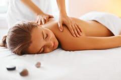 Steinmassage auf Weiß Weibliche genießende Massage in der Badekurortmitte Lizenzfreies Stockbild