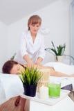 Steinmassage auf Weiß Aufbau mit Badeöl und Seifen Schönes gesundes kaukasisches Mädchen, das auf Massage-Tabelle vor Verfahren i Lizenzfreies Stockbild
